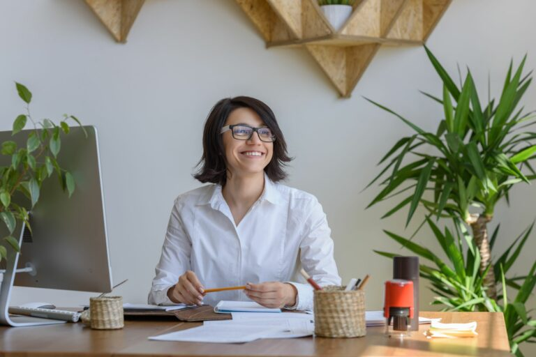 woman sitting at her home working desk smiling