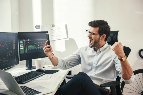 man happy looking at mobile phone in the office