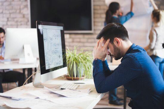 Man siting at work desk struggling to managing stress